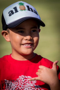 Boy giving the shaka sign at Maui Country Club